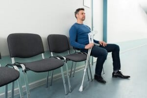 photodune-11464772-man-sitting-on-chair-with-crutches-xs-min
